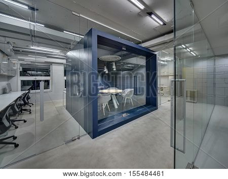 Dark blue meeting room with a furniture and a glass door in the office in a loft style with gray walls. Around it there are work zones with glass partitions. Lamps are glowing. Horizontal.