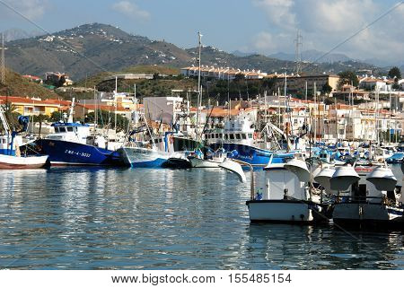 CALETA DE VELEZ, SPAIN - OCTOBER 27, 2008 - View of fishing boats and yachts moored in the harbour with town buildings to the rear Caleta de Velez Malaga Province Andalusia Spain Western Europe, October 27, 2008.