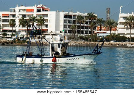 CALETA DE VELEZ, SPAIN - OCTOBER 27, 2008 - Traditional fishing boat with apartments to the rear Caleta de Velez Malaga Province Andalusia Spain Western Europe, October 27, 2008.