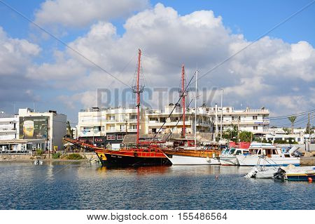 HERSONISSOS, CRETE - SEPTEMBER 14, 2016 - Yachts and boats in the port with waterfront restaurants to the rear Hersonissos Crete Europe, September 14, 2016.