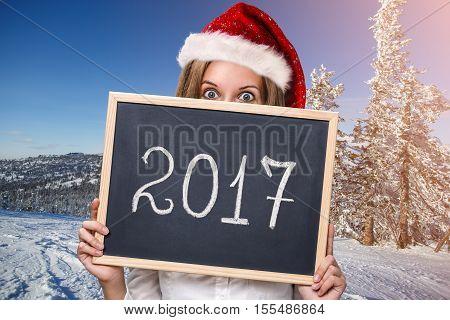 Cute girl in santa red hat with new year date on chalkboard in snowy landscape