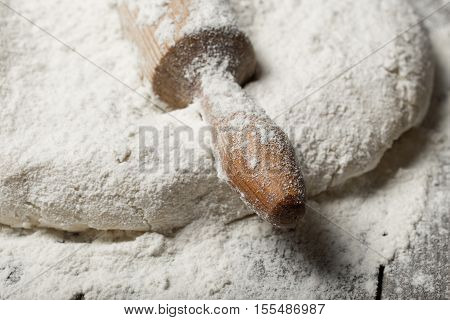 Rolling pin with flour on wooden table in bakery close up. Bakery background