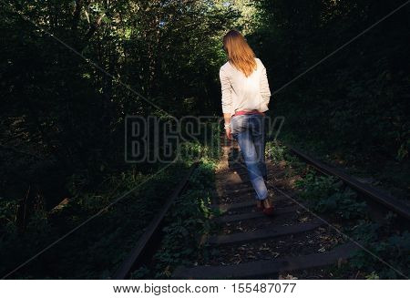 Woman walking in the sunset along the railroad tracks. Copy space