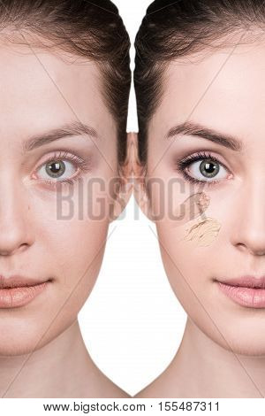 Young woman applying foundation on a skin isolated on white.