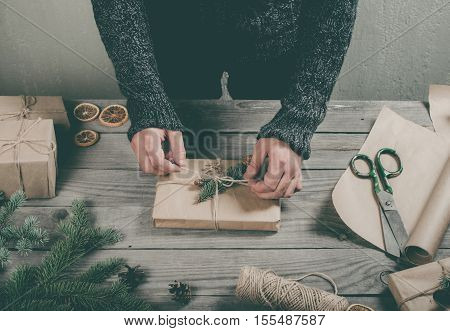 Male hands wrapping Christmas gift on wooden table close up