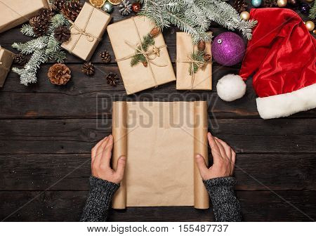 Male hand holding blank sheet of paper on dark wooden table with Christmas presents overhead view