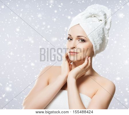 Young, beautiful and natural woman in towel over seasonal winter background. Christmas spa concept.