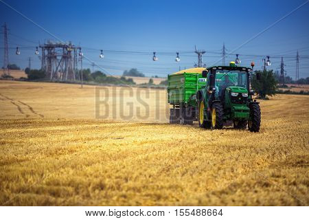 Varna Region Bulgaria - June 20 2015: A modern John Deere 6115R tractor with the trailer on a yellow field.The 6115R has Premium ComfortView cab.Full Frame design 2.580 m wheelbase and 4.5 l DieselOnly PowerTech PVX engine