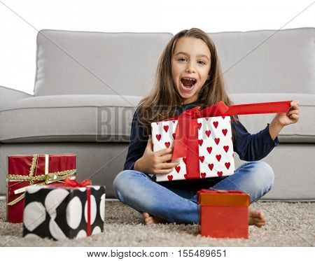 Happy little girl at home opening Christmas presents
