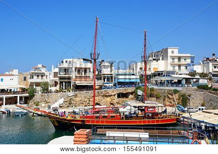 SISSI, CRETE - SEPTEMBER 14, 2016 - Black Rose Pirate ship moored in the harbour with waterfront restaurants to the rear Sissi Crete Europe, September 14, 2016.
