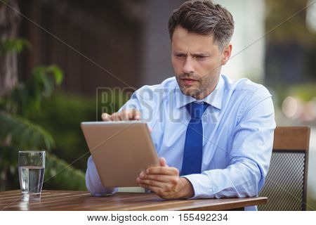 Businessman using digital tablet at outdoor café