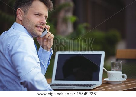 Handsome businessman talking on mobile phone while using laptop at outdoor café