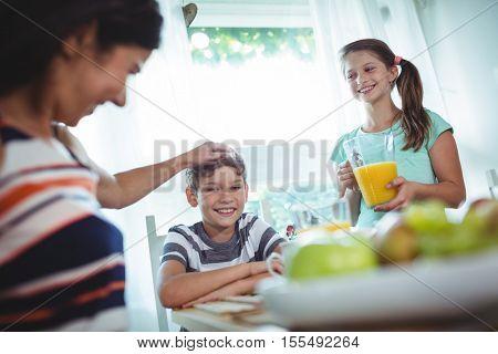 Smiling family having breakfast at home