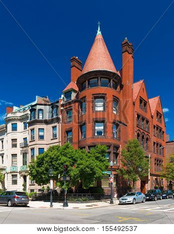 Boston, MA - July 2016, USA: Old historical building made of red brick and brownstone with cone rooftop in Boston back Bay district, against the backdrop of a clear blue sky