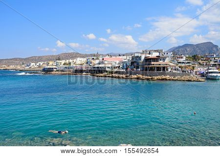 SISSI, CRETE - SEPTEMBER 14, 2016 - Woman snorkelling in shallow water in the bay with views towards the town and rugged coastline Sissi Crete Europe, September 14, 2016.