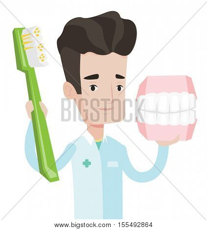 Young friendly dentist holding dental jaw model and a toothbrush in hands. Caucasian male dentist showing dental jaw model and toothbrush. Vector flat design illustration isolated on white background.
