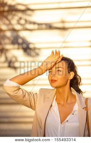 Time to travel concept. Outdoor summer portrait of young pretty cute brunette girl suffering summer heat. Beautiful woman at street against business building with shade of palm in hot day in the city.