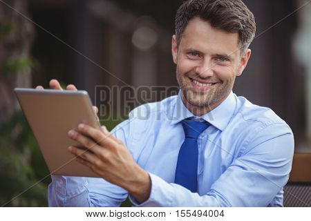 Portrait of businessman using digital tablet at outdoor cafe