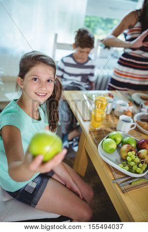 Portrait of smiling girl showing a green apple at home