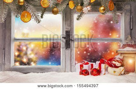 Vintage wooden window overlook winter blurry landscape. Christmas decoration on foreground