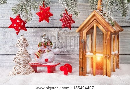 Burning lantern and christmas decoration on wooden background. Copyspace for text
