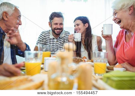 Happy couple and parents talking while having breakfast at home
