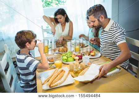 Woman cutting loaf of bread while family having breakfast at dinning table