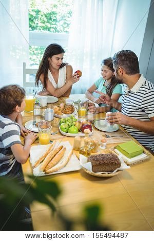 Happy family talking to each other while having breakfast together at home