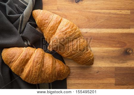 Two buttery croissants on wooden table with brown napkin. Top view.