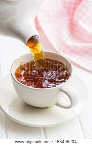 Pouring tea from teapot into a cup.