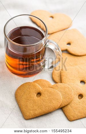 Gingerbread heart shape and glass cup of tea.