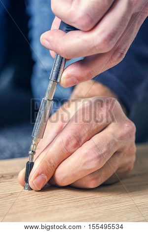 Man assembling furniture at home on the floor hand with screwdriver