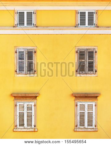 Building facade and old windows with classic wooden venetian shutters blinds mediterranean europe architecture vintage style