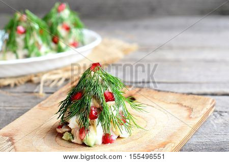 Salad Christmas tree. Salad with meat, mushrooms, cucumbers and eggs decorated with dill and pomegranate. Christmas appetiser. Old wooden background with copy empty space for text