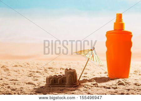 Sunscreen, sand castle and umbrella on the seashore.
