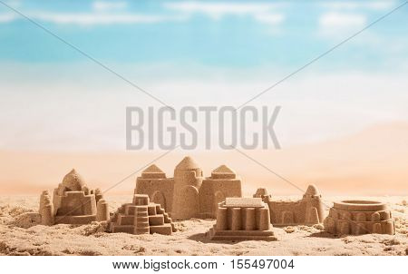Sand castles, towers and Coliseum on the background of the sea.