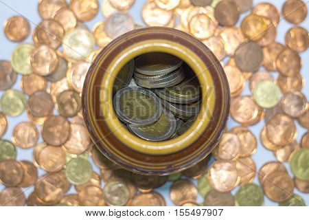 Thai coins in a jar and a  king and queen on a coin.