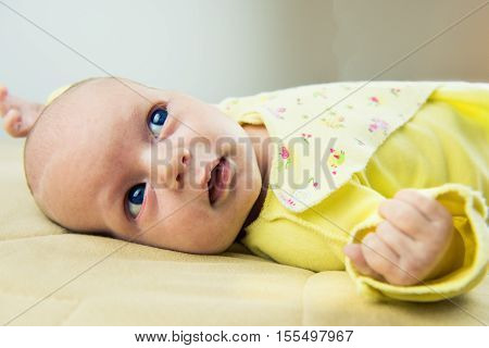baby lying on a bed in light yellow shirt