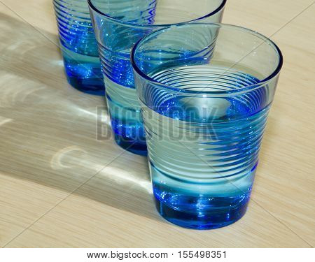 Three blue glasses of water on the beige wooden background