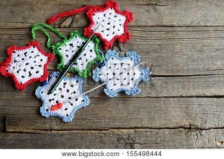 Snowflakes crocheted from cotton yarn, two hooks on an old wooden background with copy space for text. Easy winter crafts for children and beginners. Crochet home ornaments
