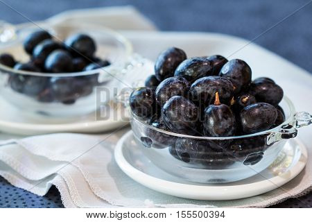 Black grapes in a small clear glass bowl on a white saucer. Another bowl with grapes in the background. A healthy and nutritious dessert or snack.