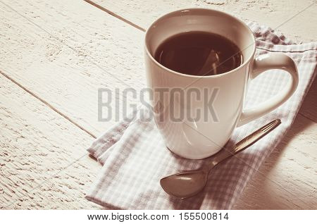 Cup of coffee on a white wooden background. Vintage toning. Selective Focus