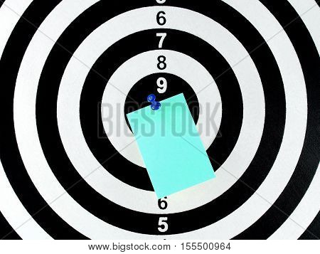close-up blank blue paper note with blue pushpin on target center of dartboard, message for goal and achievement