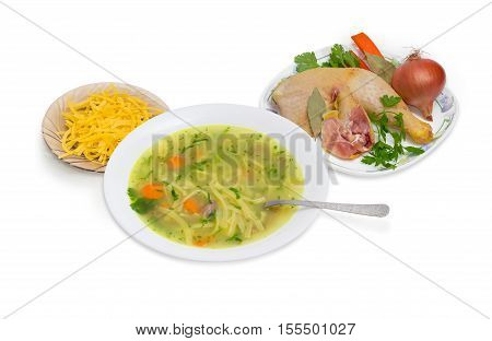 Homemade chicken noodle soup in white dish with spoon and ingredients for its cooking on a light background