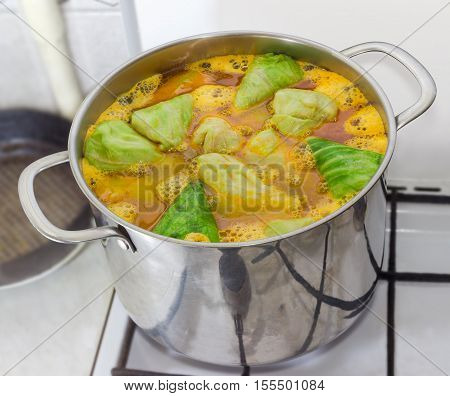 Stuffed cabbage rolls in boiling sauce in large stainless steel saucepan during cooking