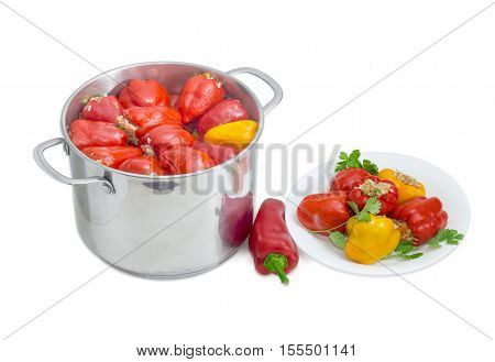 Cooked stuffed red and yellow bell peppers in a large stainless steel saucepan fresh red bell pepper and white dish with several Stuffed peppers on a light background