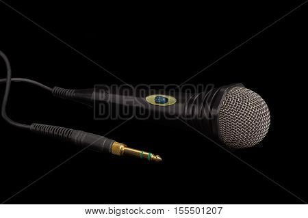 Dynamic microphone in black plastic housing with windscreen in wire mesh and its phone connector on a dark background