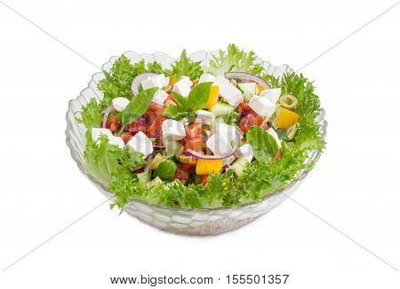 Greek salad decorated with lettuce and basil leaves in a glass salad bowl on a light background