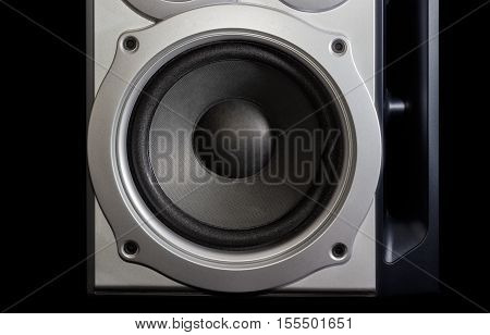 Fragment of a home loudspeaker in silvery housing with woofer closeup on the dark background