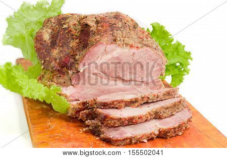 Partly sliced big piece of baked pork neck on cutting board closeup on a light background